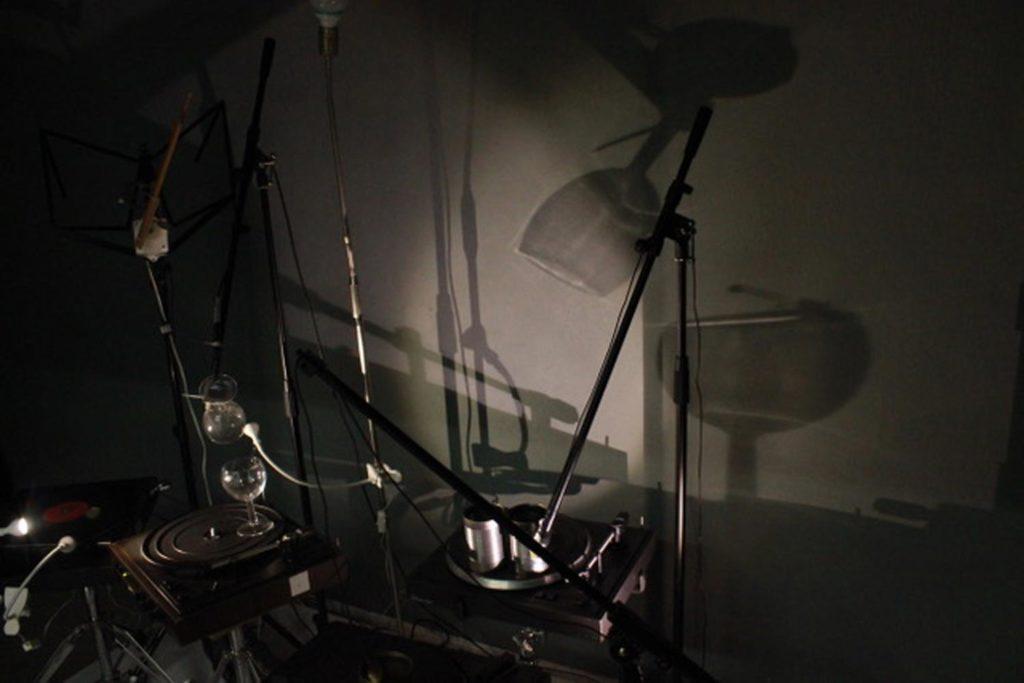 """Jana Debrodt, """"Selbstgespräch, 2017"""", Klanginstallation: 4 Plattenspieler, 2 Motoren, 6 Kleinstrahler, 4 Mikrofonständer, 1 Notenständer, 1 Radio, 1 Lampe, 3 Blechdosen, ein Glas, ein Schlagzeugstick, 4 Klangstäbe, Vinylplatten und 5 Piezotonabnehmer, ca. 100 x 200 x 150 cm, Foto: © Jana Debrodt (VG Bild Kunst)"""